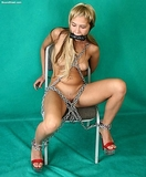 Butt Naked, Heavy Chains Hold Her Fast. Butt naked and chained a cold steel chair. Watch her struggle ... see her cute little snatch ... is this a turn on for her?