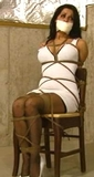 Chair Tied Struggle. Tightly roped to her chair and tape gagged for her paid fantasy abduction in her dress and high heels. From RopExpert.com
