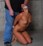 Jade Stripped Naked, Bound & Gagged. Forced at gun point to gag herself, stripped naked, bound on camera and fondled.   Nude, tape gagged, tits, bare feet