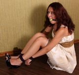 Very cute frilly sexy dress, open toed stiletto high heels, ball gagged, wrists roped to ankles.
