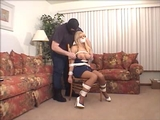 Tightly bound to a straight backed chair in her sexy little jean dress with a zipper down the front. Stiletto high heels, pantyhose and great cleavage. I don't think she's happy at all. Wait, what is