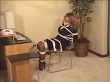 Sexy secretary tightly tied to her chair wearing a business suit, stockings and sexy strappy high heels. Watch as she scoots her chair across the floor attempting to escape. No luck! She isn't happy..